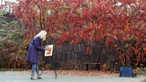 The young girl paints a picture in the autumn park. Beautiful blonde girl in the purple coat painting a picture on an easel, holding paints in hand. Colorful stock photos