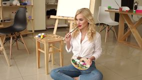 A young girl with a palette and brushes sitting on the floor in an art Studio. stock video