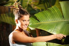 Young girl and a palm tree leaf Stock Photo