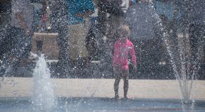 Young girl palying in water fountain royalty free stock images