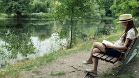 A young girl reading a book on a bench near the lake. A young girl in panama sits on a bench and reading a book in the city park on the lake stock video footage