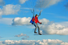 The young girl parachutist in cloudy sky Stock Image