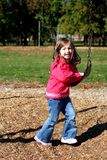 Young girl in the park. A young 4 year old girl playing in the park on a sunny fall day. She is having fun on the swings Royalty Free Stock Images