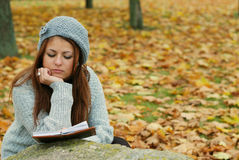 A young girl in the park. A young girl with a book in the park Royalty Free Stock Photos