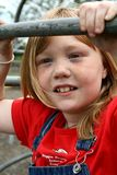 Young Girl at the Park. Young girl with red hair and freckles playing on the bars at the park Stock Images