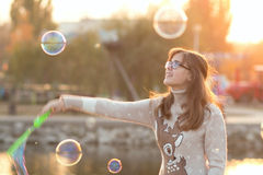 Young girl in the park blow bubbles Royalty Free Stock Image
