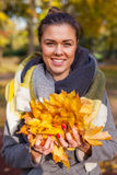 Young girl in park with bouquet of leaves. Autumn time. Royalty Free Stock Photo