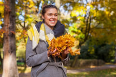 Young girl in park with bouquet of leaves. Autumn time. Royalty Free Stock Photos
