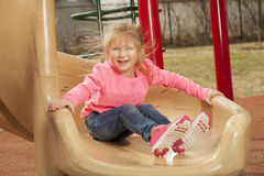 Young girl at the park. A young girl has fun at the park while going down the slide royalty free stock photo