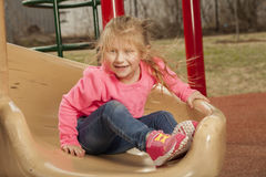 Young girl at the park. A young girl has fun at the park while going down the slide royalty free stock photos