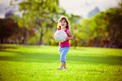 Young girl in the park holding white ball Royalty Free Stock Image