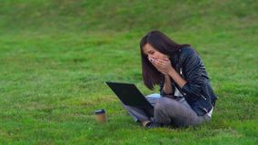 Young girl in the Park with a laptop. He receives a message in the mail and is very happy. stock video