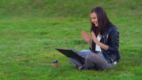 Young girl in the Park with a laptop. He receives a message in the mail and is very happy. stock footage