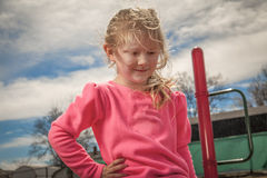 Young girl at the park. Looking down and with a smile stock photo