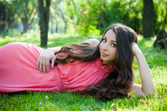 Young girl in a park. Pretty young girl in a pink dress with long hair posing in the park laying in a grass, forest fairy's portrait stock image