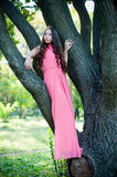 Young girl in a park. Pretty young girl in a pink dress with long hair posing in the park on a tree, forest fairy royalty free stock images