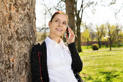 Young girl in park talking on the phone Royalty Free Stock Photos