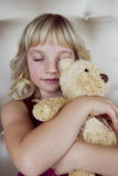 Young girl in party dress, holding a teddy bear Royalty Free Stock Photos