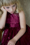 Young girl in a party dress looking bored and unhappy Royalty Free Stock Photos