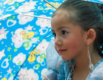 Young Girl in Pase del Niño Parade. A young girl under an umbrella and in costume as she moves along the parade route of the Pase del Niño parade, Cuenca Royalty Free Stock Photos