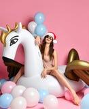 Young girl with pastel air balloons on birthday holiday party having fun celebrating with unicorn pegasus float. Beauty girl celebrating xmas new year on unicorn stock image