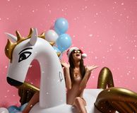Young girl with pastel air balloons on birthday holiday party having fun celebrating with unicorn pegasus float in Santa hat. Beauty girl celebrating xmas new royalty free stock images