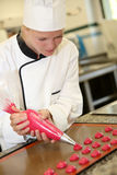 Young girl in pastry school. Pastry cook student making red cookies Stock Photo