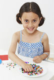Young girl paying with beads Royalty Free Stock Images