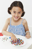 Young girl paying with beads Royalty Free Stock Photo