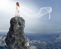 Young Girl, Peace, Hope, Love. A young girl stands above the mountains on a rock or cliff. Abstract concept for peace, love, hope, spiritual rebirth, innocence Stock Images