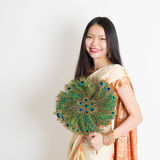 Young girl with peacock feather fan in Indian sari dress stock image