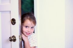 Young girl peeking into new house. Young cute girl peeking into new house Royalty Free Stock Images