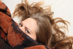Young girl peeking out from under the blanket Stock Photography