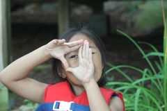 Young Girl Peeking thru formed fingers. Cute young girl with scratches on her nose and lip from a fall, looking through formed fingers, wearing a life jacket Royalty Free Stock Images