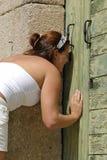 Young girl peeking trough a keyhole. Curious young girl peeking trough a keyhole Stock Images