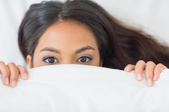 Young girl peeking from under the duvet Stock Photo