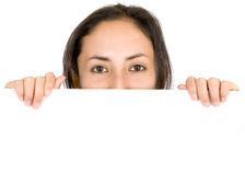 Young girl peeping over a white banner Royalty Free Stock Photography