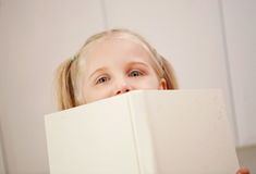 A young girl peers over a book Stock Photo