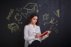 Young girl, pencil marks something in an open book, standing near a board with images of science signs. stock photo