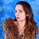 Young girl with a pendant dressed in a fur coat Stock Photography