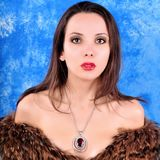 Young girl with a pendant dressed in a fur coat Stock Photo
