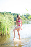 Young girl with perfect legs in pink swimsuit Stock Photography