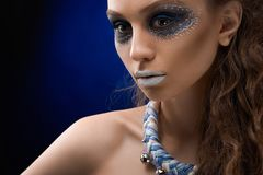 Young girl with perfect skin and bright make-up. The portrait of a young and beatiful girl with the artistic make-up on the dark blue background . She has Stock Image