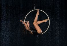 A young girl performs the acrobatic elements in the aerial hoop. Black Aqua Studio stock images