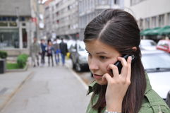 Young girl performs a call to a mobile phone. In hurry Royalty Free Stock Photo