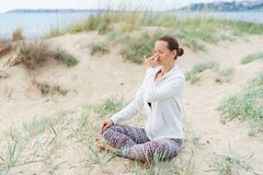 Young girl performs morning breathing practices of pranayama Nadi Shodhana on the beach in summer stock photo
