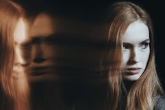 Young girl with personality disorder. Against black background with blurred face royalty free stock photography
