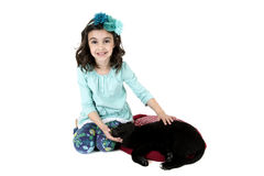 Young girl petting black lab puppy smiling at camera Stock Photography