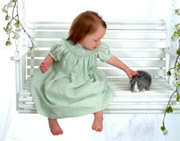 Young Girl Petting Bunny. Young girl in green petting bunny on swing Stock Photos
