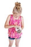 A young girl petting the stomach of her pet hedgehog. On an isolated white background Stock Photo